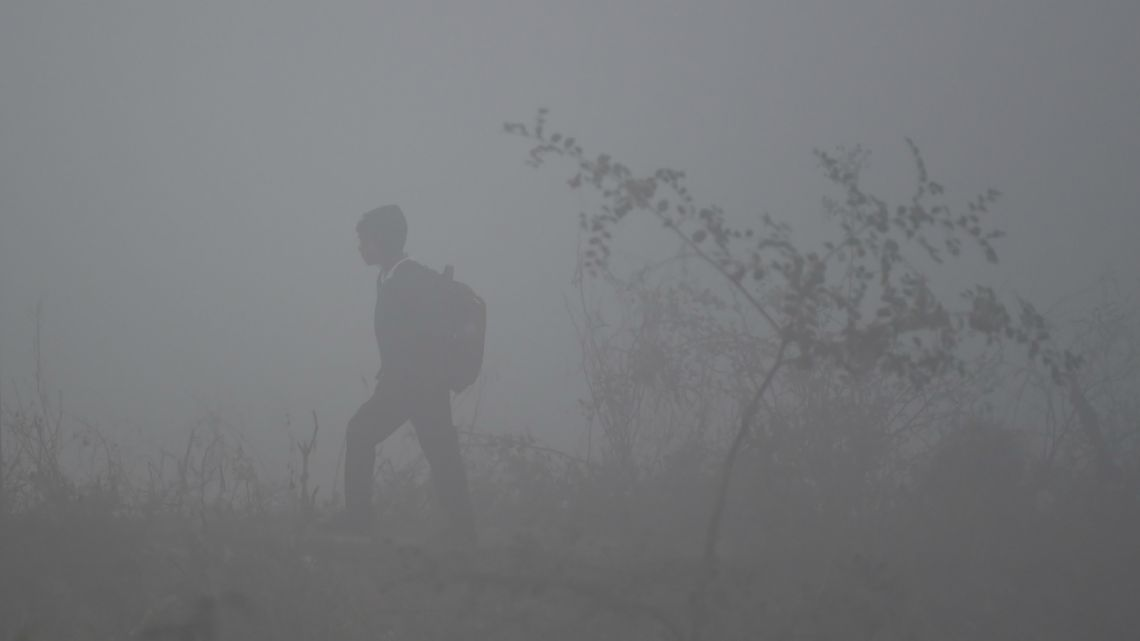 A boy walks to school amidst heavy fog in Faridabad on January 21, 2020.