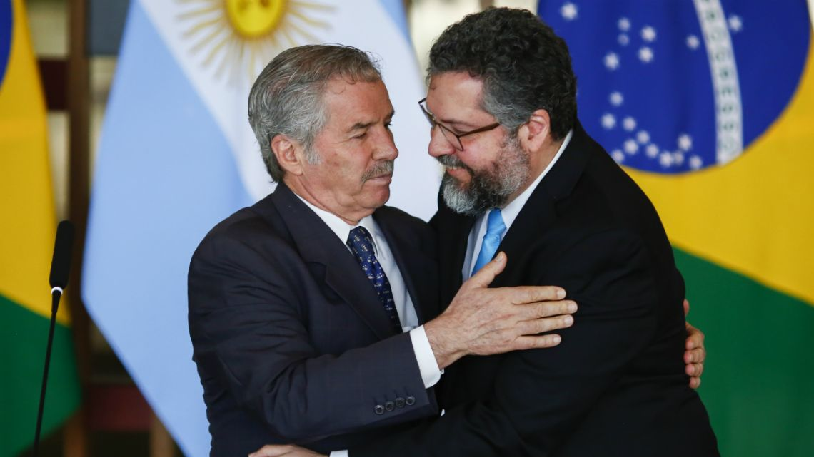 Brazilian Foreign Minister Ernesto Araujo (Right) hugs Argentine Foreign Minister Felipe Sola (left) during a press conference at the Itamaraty Palace, in Brasilia, Brazil, on February 12, 2020.