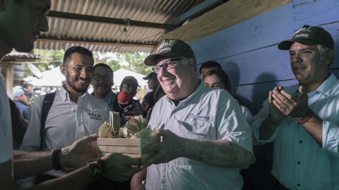 Howard Buffett receives presents during a visit, with Colombia's President Ivan Duque, right, to a cocoa farm in La Gabarra, Colombia.