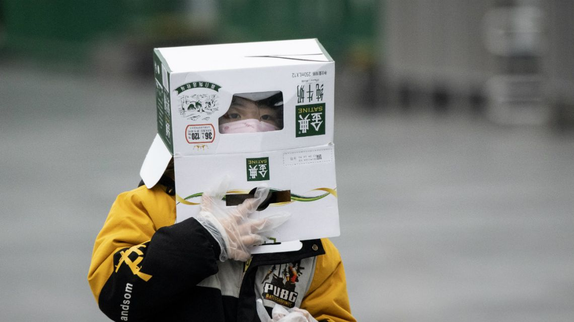 A boy wears a cardboard box on his head at the Shanghai Railway station in Shanghai on February 13, 2020.