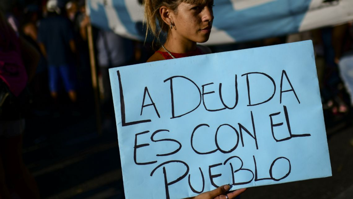 "People protest against the International Monetary Fund (IMF) outside of the Argentine Congress, on February 12, 2020. The sign partly reads, ""the debt is with the people."""