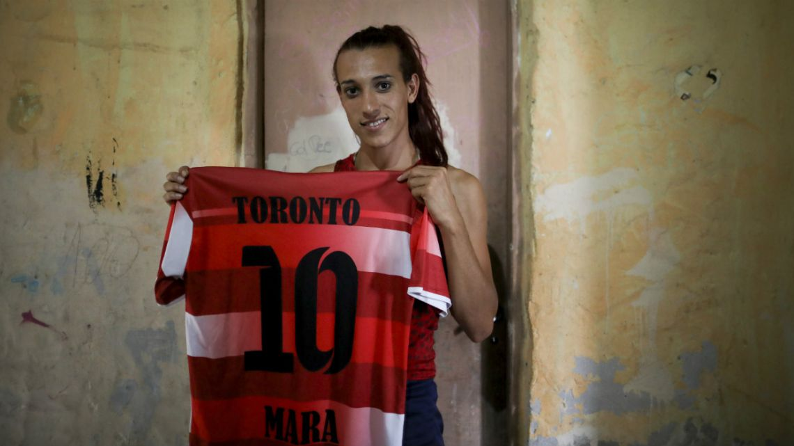 Soccer player Mara Gómez poses with her old jersey from the first amateur soccer club she played for, Toronto, in La Plata, Argentina.