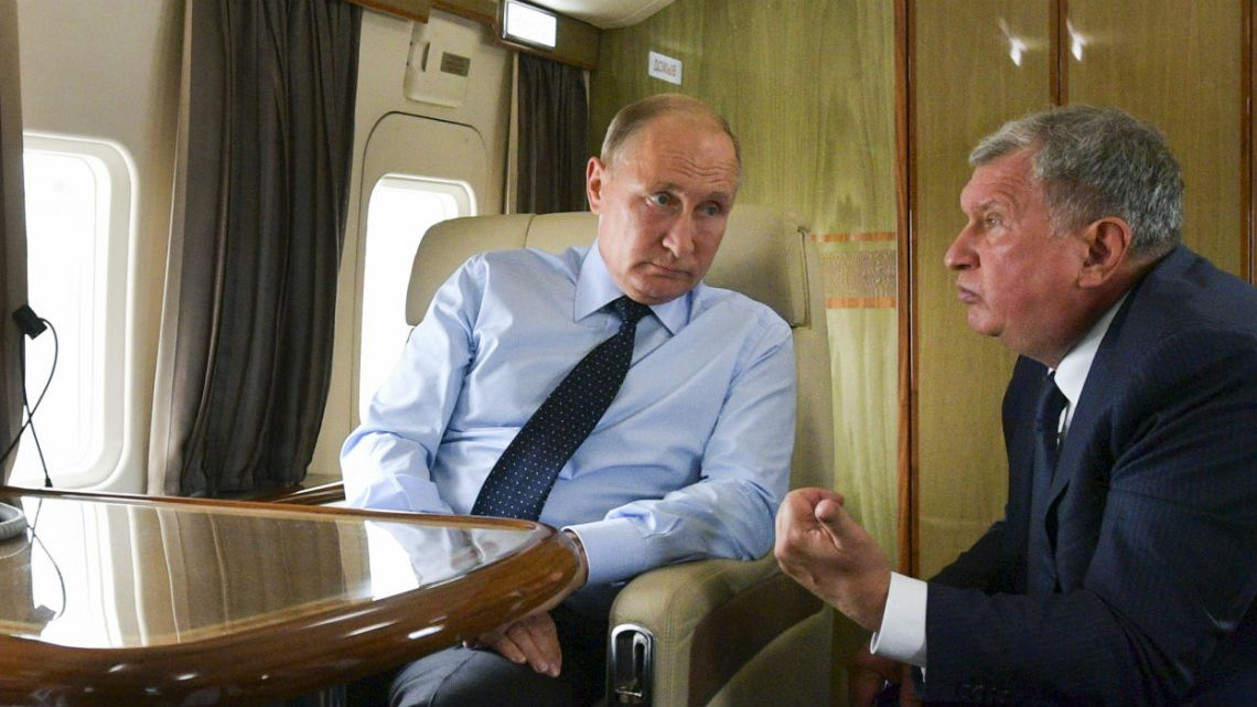 Russian President Vladimir Putin, left, listens to Russian Rosneft CEO Igor Sechin during his flight to visit Chernigovets coal mine, in Beryozovsky, Kemerovo region, Russia.