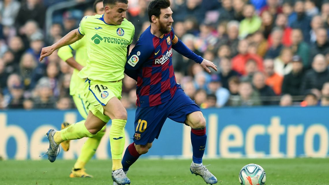 Getafe's Uruguayan midfielder Mauro Arambarri (L) challenges Barcelona's Argentine forward Lionel Messi during the Spanish league football match between FC Barcelona and Getafe CF at the Camp Nou stadium in Barcelona on February 15, 2020.