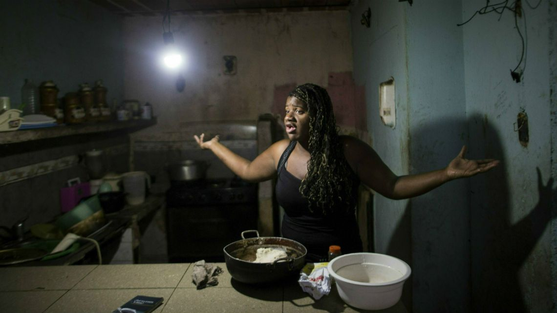 Dugleidi Salcedo complains to a neighbor about the high price of food as she prepares arepas for her three sons in her kitchen in the Petare slum, in Caracas, Venezuela.