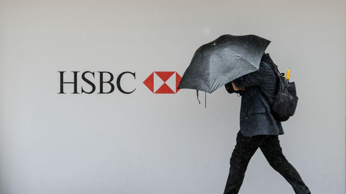 A pedestrian shields himself from the rain as he walks past an HSBC advert in Hong Kong on August 3, 2016.