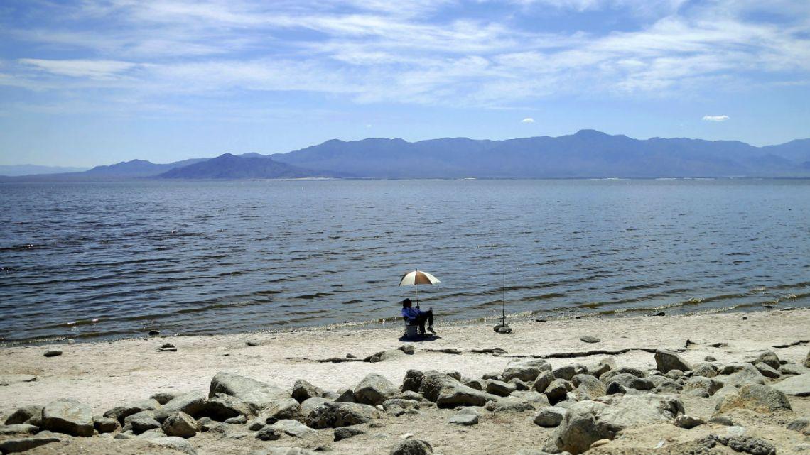 A man fishes along the receding banks of the Salton Sea near Bombay Beach, California.