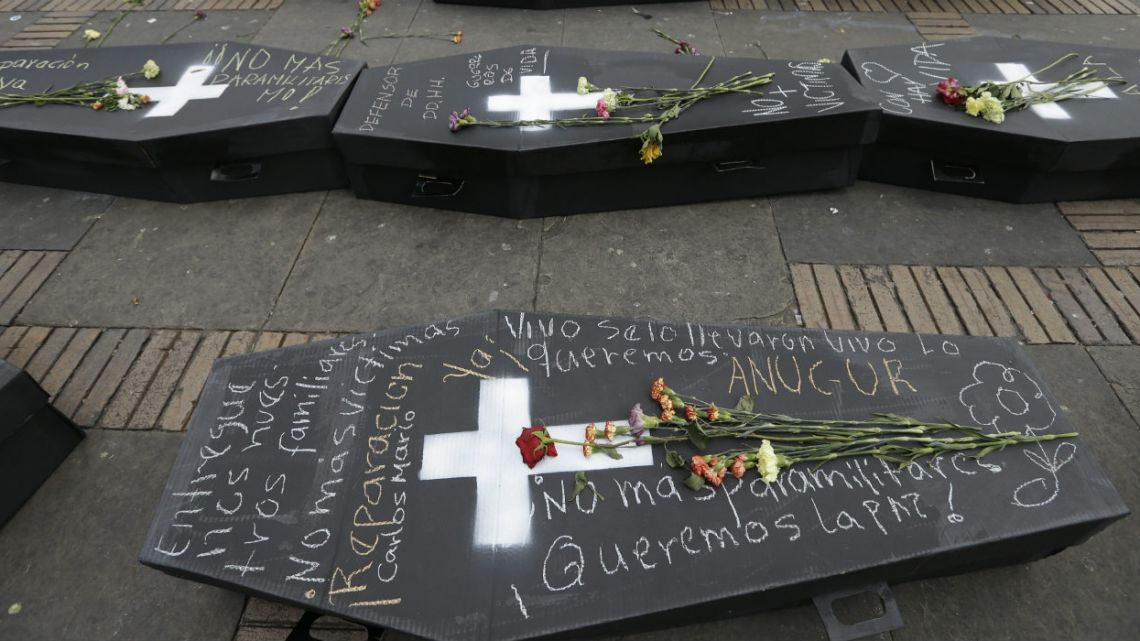 Flowers lay on symbolic caskets that represent victims of Colombia's civil conflict at Bolivar square in Bogota, Colombia.