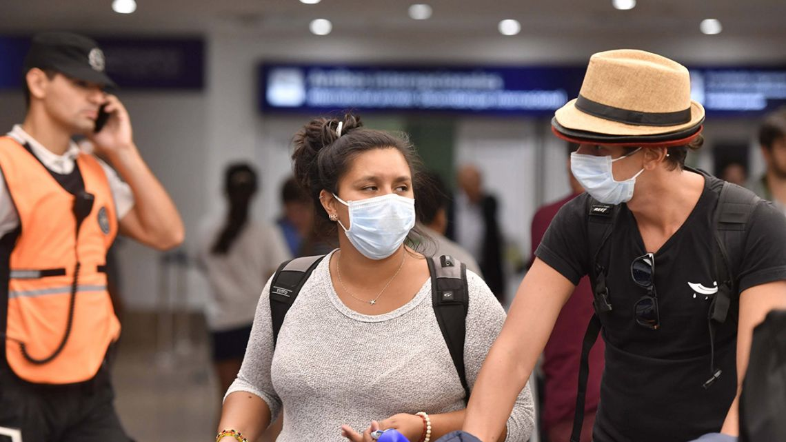 Passengers exit Ezeiza international airport using surgical face masks, in a bid to protect themselves against coronavirus.