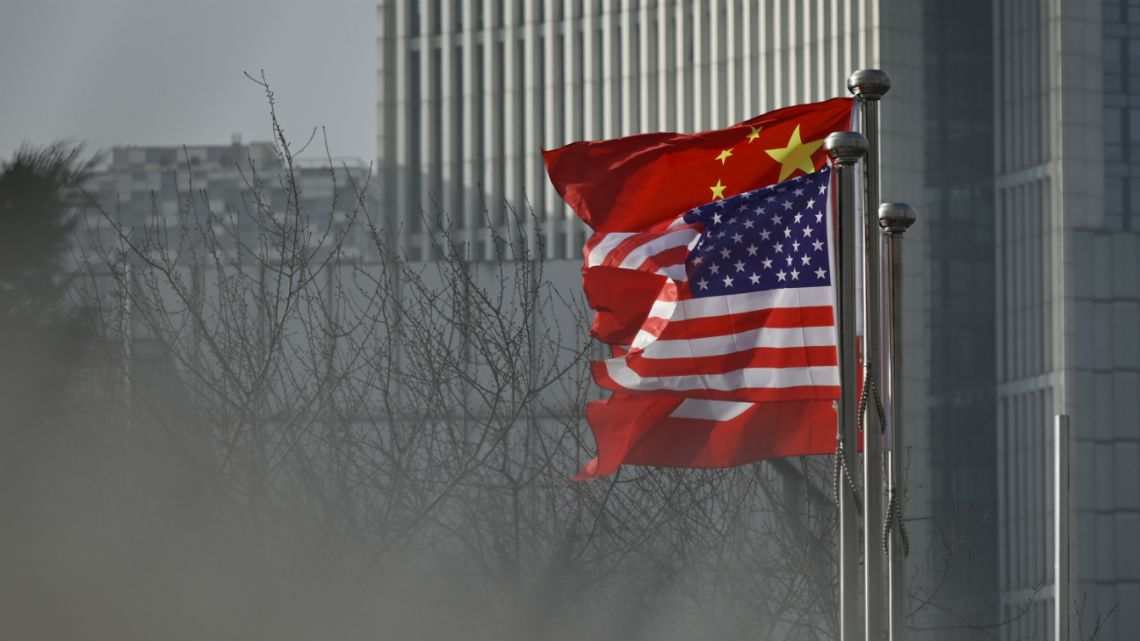 In this file photo taken on January 18, 2020 Chinese and US national flags flutter at the entrance of a company office building in Beijing.