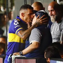 Carlos Tevez gives Diego Maradona a huge kiss before the match.