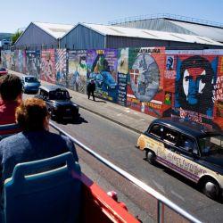 Turistas en un tour en autobús en Belfast observan graffitis con mensajes políticos. Foto: Tourism Ireland/dpa-tmn