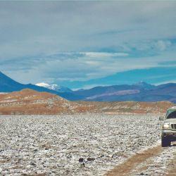 Los vehículos cruzan el Salar de Antofalla, rumbo a Inca Huasi; detrás, el volcán Peinado.