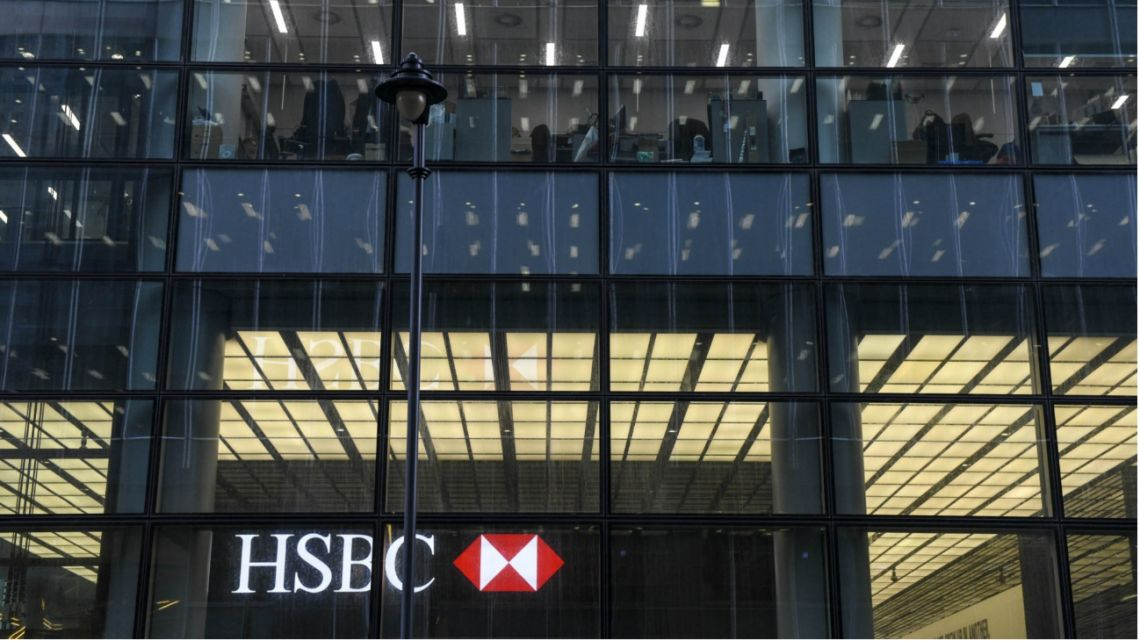Empty desks sit above a HSBC Holdings Plc logo at their office building in the Canary Wharf financial, business and shopping district of London, UK, on Thursday, March 5, 2020.