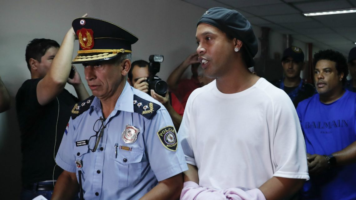 Former soccer star Ronaldinho talks as he walks escorted by Police officers with hands handcuffed to declare to judge Clara Ruiz Diaz at Justice Palace in Asuncion, Paraguay.