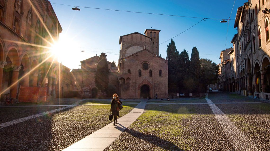 A woman walks past the Basilica of Santo Stefano, in Bologna, Italy, Wednesday, March 11, 2020. The Italian government extended a coronavirus containment order previously limited to the country's north to the rest of the country beginning Tuesday, with soldiers and police enforcing bans.