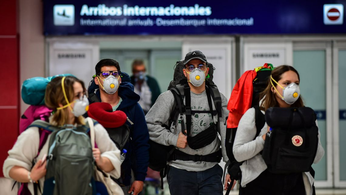 Passengers wearing face masks as a preventive measure against the spread of the Covid-19 coronavirus arrive at Ezeiza International Airport in Buenos Aires