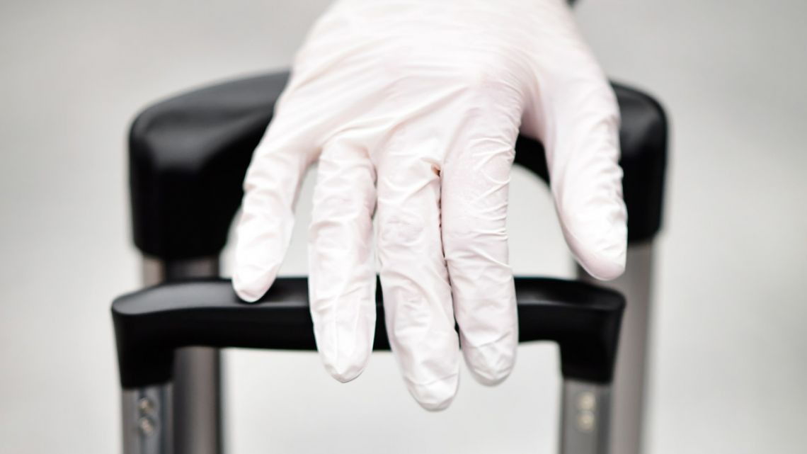 A person uses gloves as a preventive measure against the spread of the COVID-19 coronavirus.