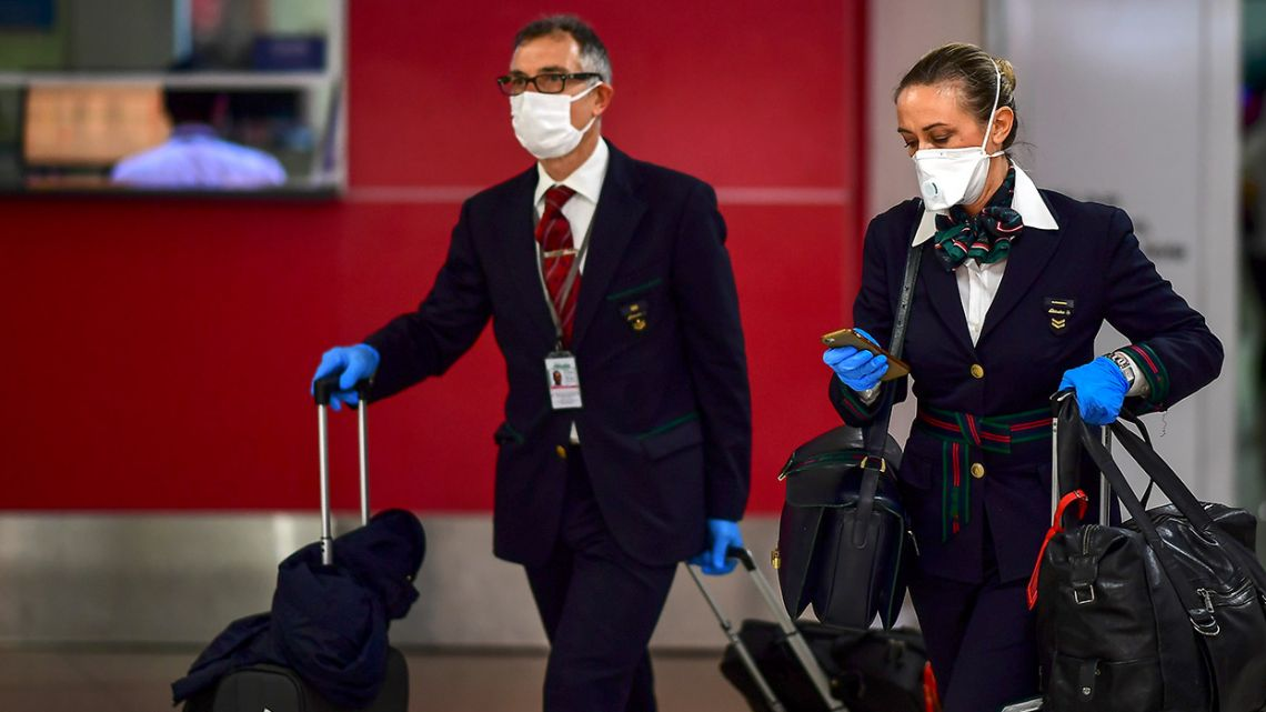 Crew members wearing face masks as a preventive measure against the spread of the Covid-19 coronavirus arrive at Ezeiza International Airport in Buenos Aires.