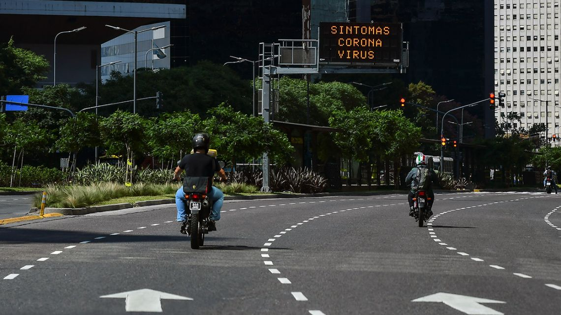 Two bikers ride in front of an electronic traffic board displaying a message on the Coronavirus symptoms on Avenida Libertador.