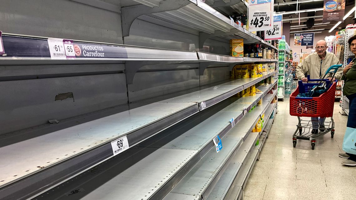 A couple walk next to the empty shelves of a supermarket, as a result of purchases for quarantine due to the Coronavirus, in Buenos Aires.