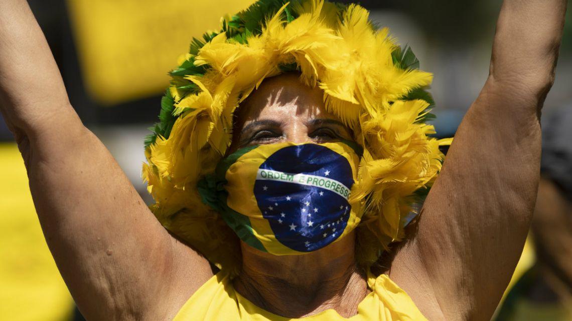 A woman covers her face with a Brazilian flag during rally supporting Brazil's President Jair Bolsonaro on Copacabana beach, Rio de Janeiro.