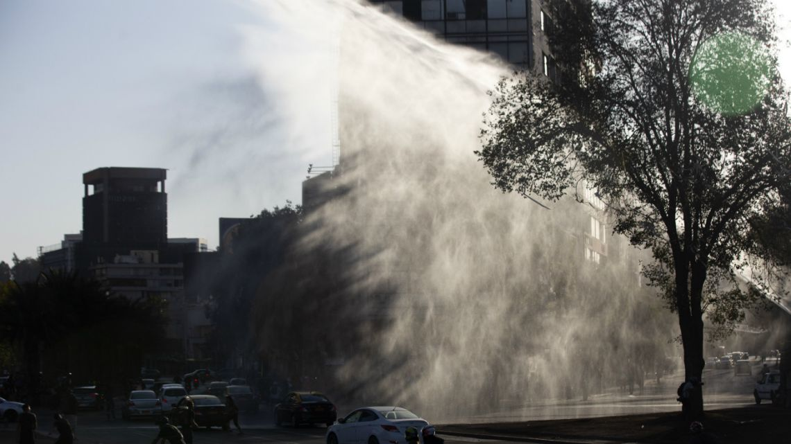 Riot police spray water to disperse a little number of demonstrators during a protest against Chilean President Sebastian Pinera's government in Santiago on March 16, 2020.