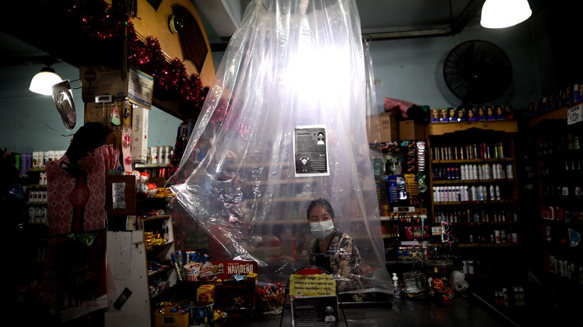 A supermarket cashier waits for costumers behind a makeshift plastic curtain as a precaution against the spread of the new coronavirus, in Buenos Aires.