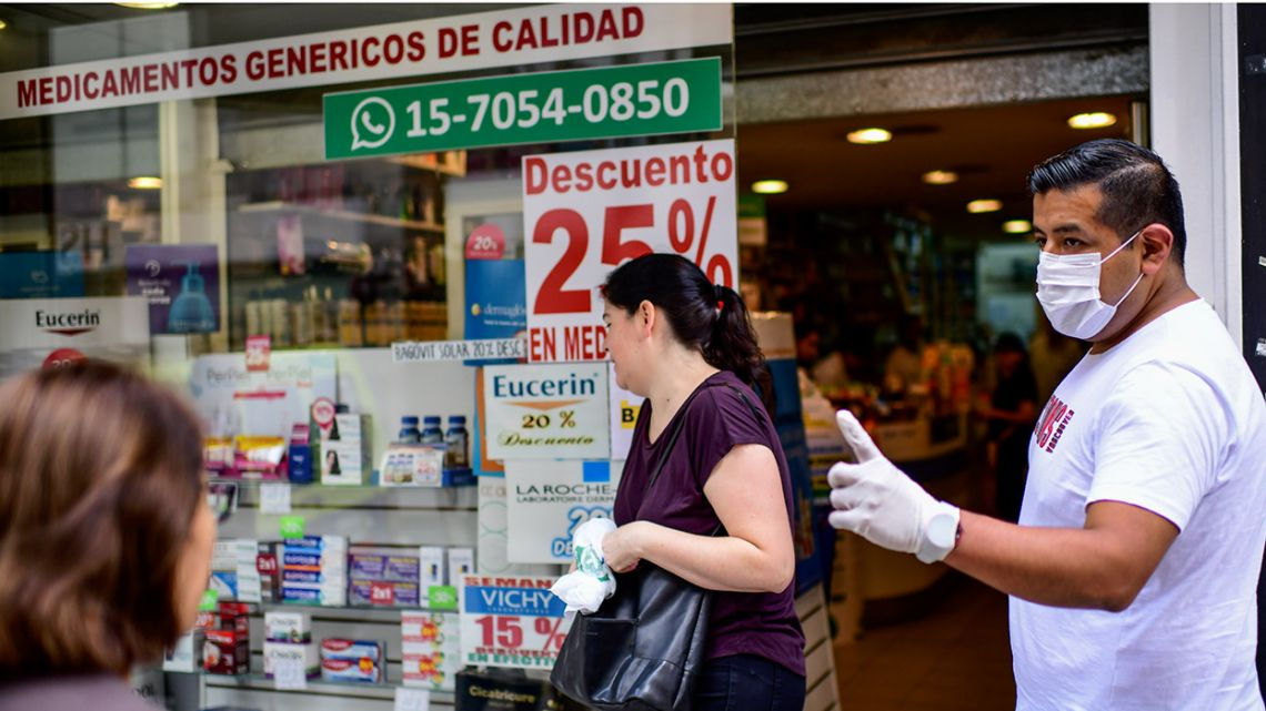 A pharmacy-worker wearing a face mask talks to customers outside a pharmacy in Buenos Aires.