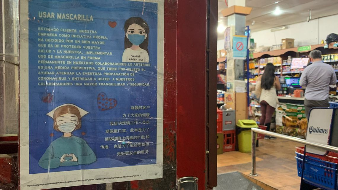 A banner written in Spanish and Chinese explains the use of surgical masks for employees at a supermarket in Buenos Aires.