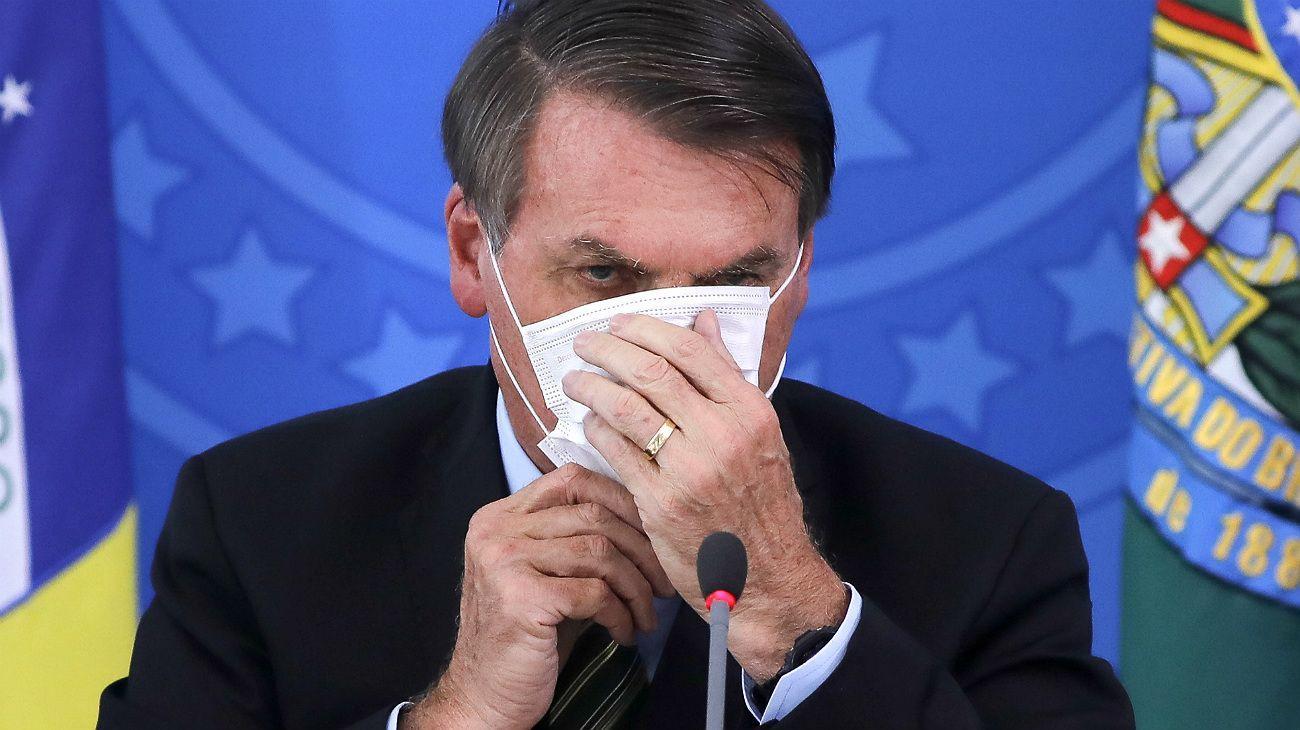 Bolsonaro, con barbijo en conferencia de prensa. Su tibia reacción contra el coronavirus genero criticas y hubo cacerolazos en Brasil.