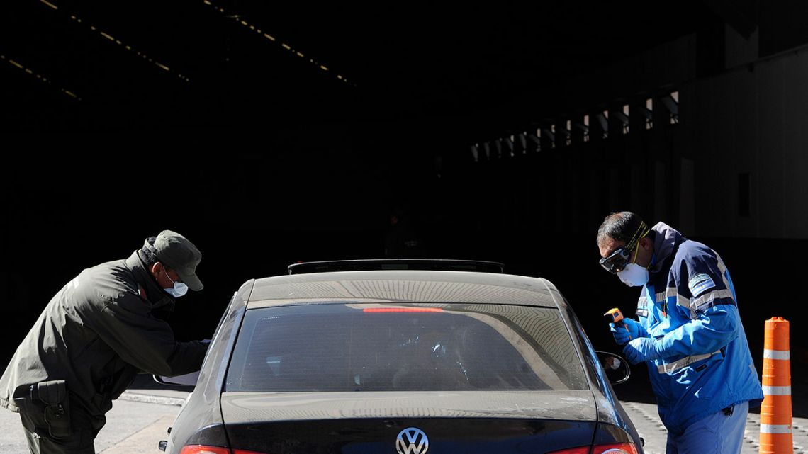 Argentine officials wearing face masks check a car entering from Chile at the Horcones border crossing in Mendoza, Argentina, after the two countries restricted control at their borders as a precaution against the spread of the new coronavirus.