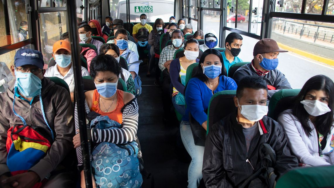 People wearing protective masks as a precaution against the spread of the new coronavirus travel on a bus in Caracas, Venezuela.