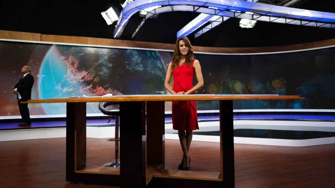 Diana Zurco poses for a photo at the table for news anchors during a rehearsal for her debut as the country's first transgender newscaster.