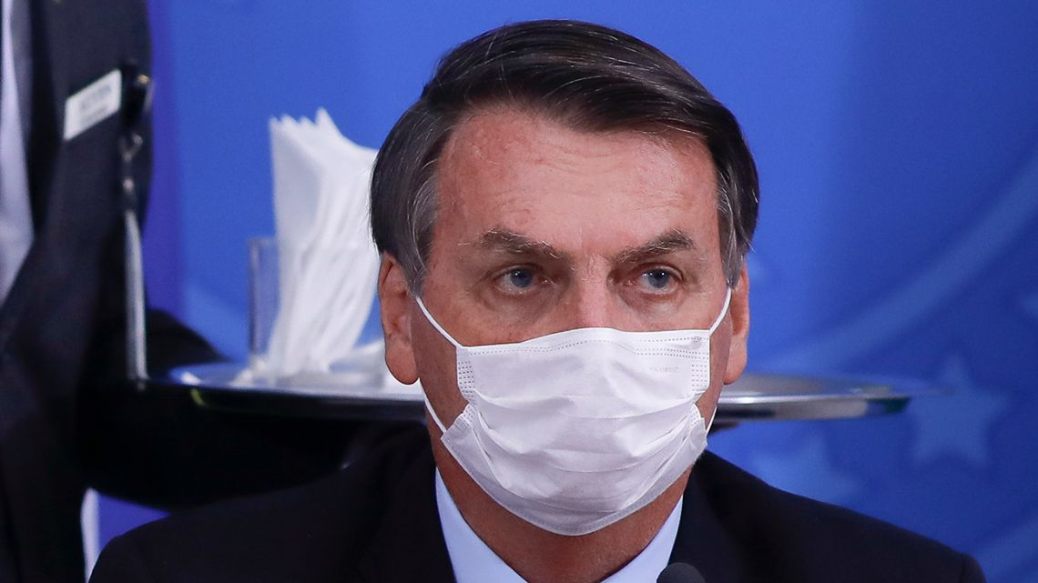 Brazilian President Jair Bolsonaro covers his face with a face mask during a press conference regarding the Covid-19 coronavirus pandemic at the Planalto Palace, Brasilia on March 18, 2020.