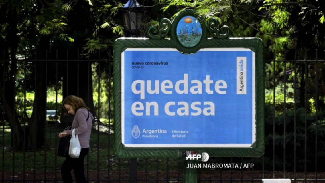 "A woman walks near a board advertising Health Ministry advise reading ""Stay at home"" during the outbreak of the new Coronavirus, COVID-19, in Buenos Aires, Argentina on March 19, 2020."