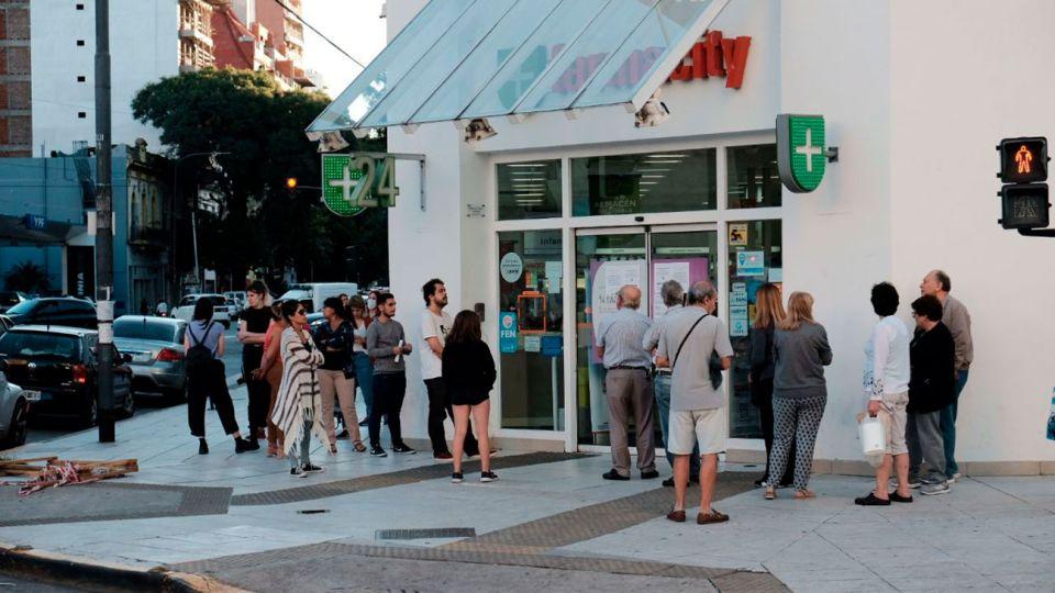 Personas haciendo fila para entrar a Farmacia