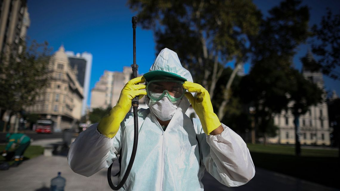 A worker adjusts his goggles as he sprays bleach at Plaza de Mayo in Buenos Aires Friday, March 20, 2020.