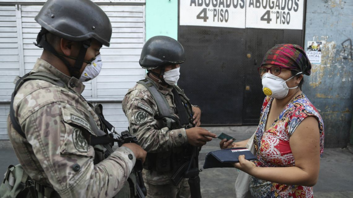 A woman explains to soldiers that she is searching pharmacies for alcohol, before they let her continue on her way, on the third day of a state of emergency in Lima, Peru.