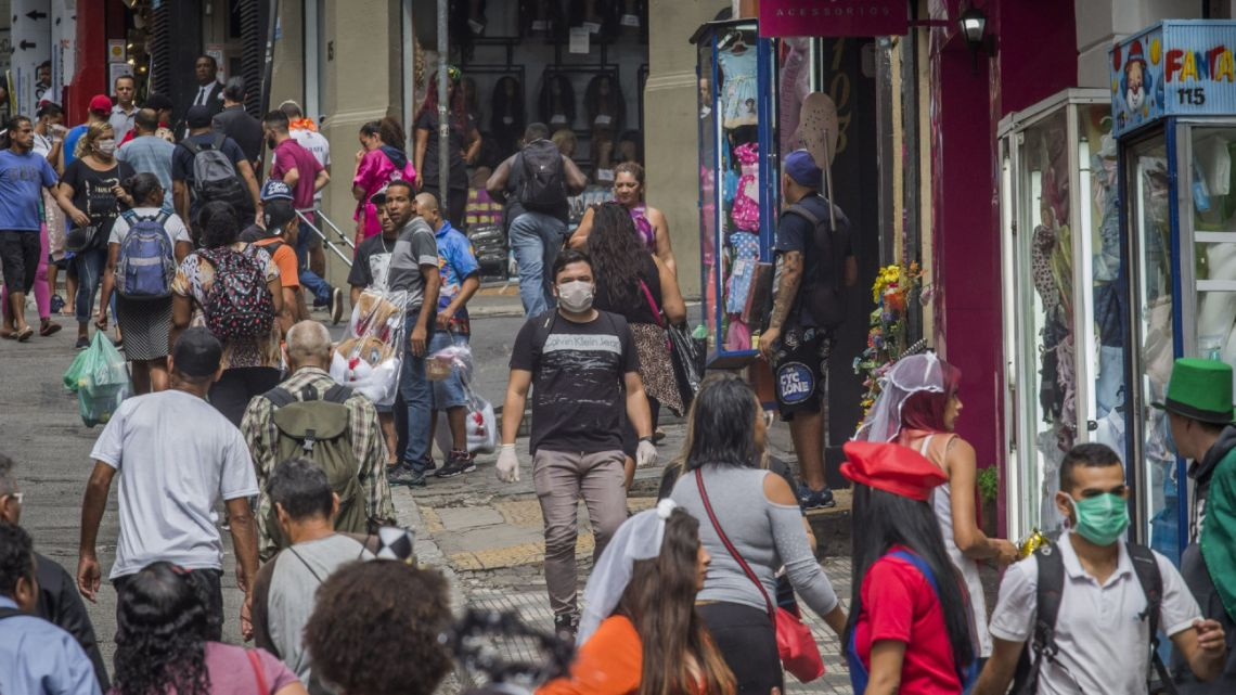 Pedestrians wearing protective masks walk down a street in Sao Paulo, Brazil, on Thursday, March 19, 2020.