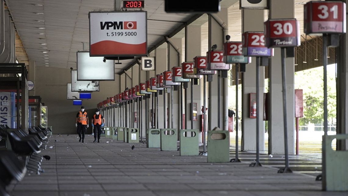 Police officers walk through an empty bus terminal in Retiro.