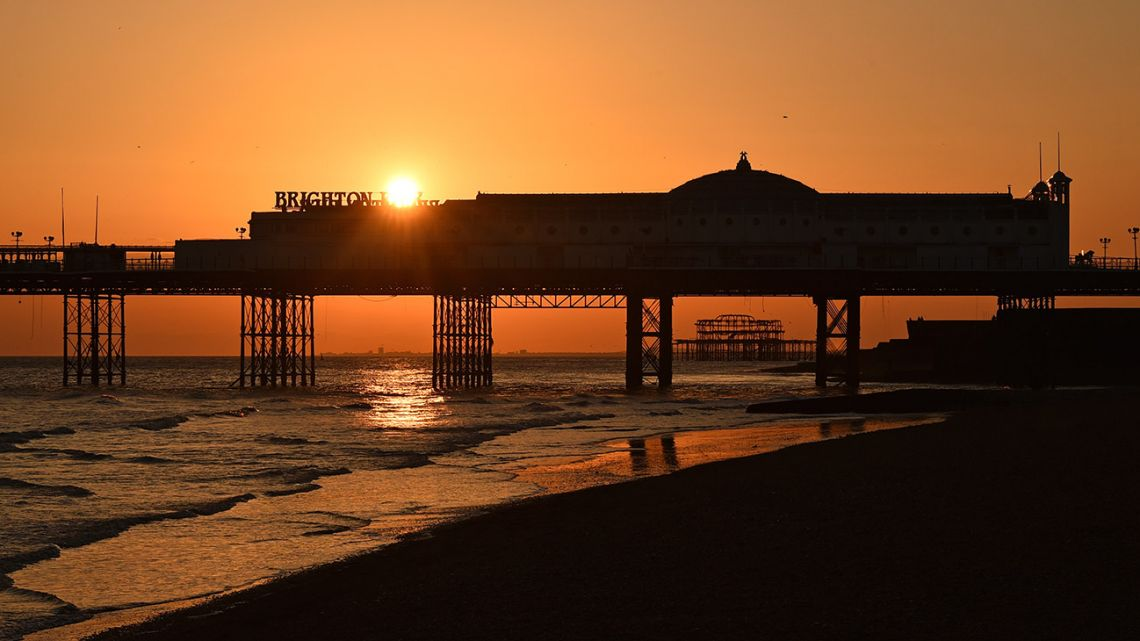 The sun sets behind the derelict West Pier and closed Palace Pier in Brighton, on the south coast of England on March 22, 2020.