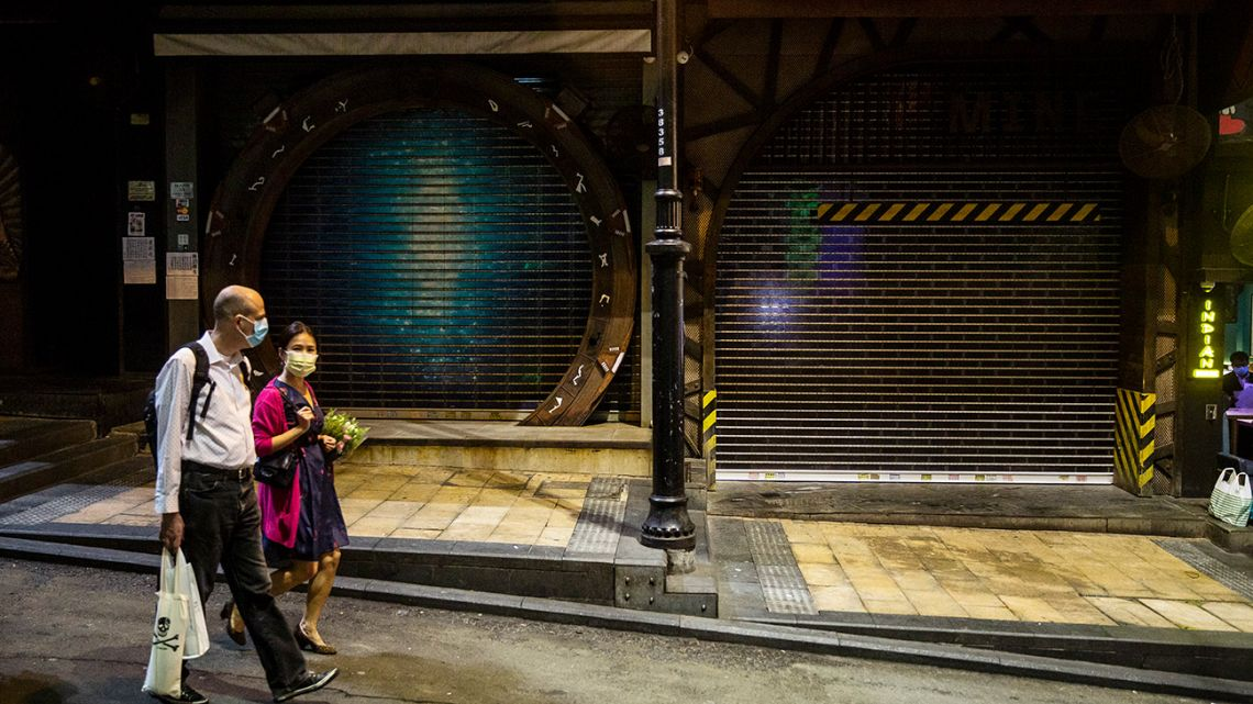 A couple wearing facemasks amid concerns over the spread of the Covid-19 novel coronavirus, walks past a closed bar in Lan Kwai Fong, a popular night district that recently saw some bars shut due to coronavirus outbreak, in the central district of Hong Kong on March 21, 2020.
