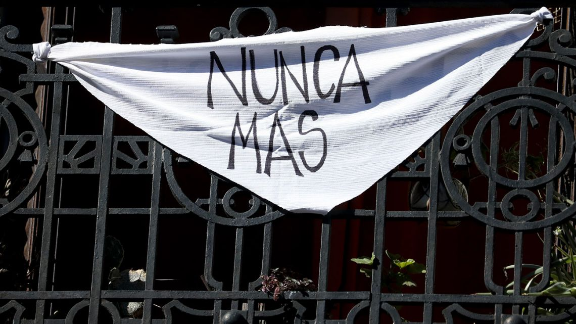 "A white handkerchief with the message ""Nunca más"" hangs from a balcony in Buenos Aires, Tuesday, March 24, 2020."