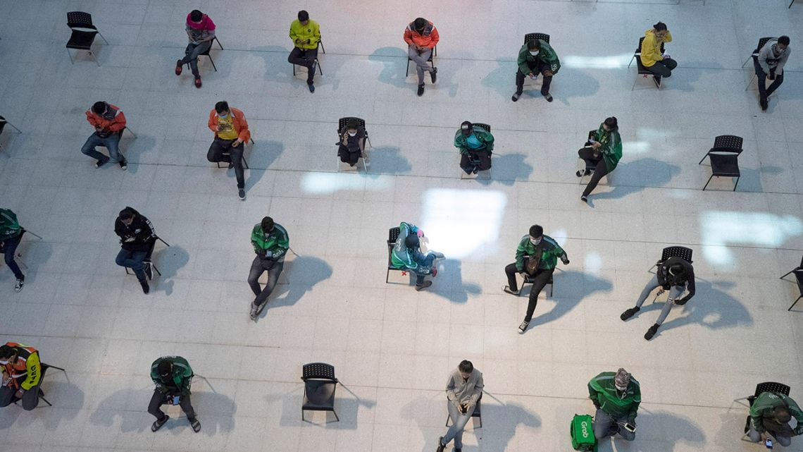 People practice social distancing as they sit on chairs spread apart in a waiting area for take-away food orders at a shopping mall in hopes of preventing the spread of the coronavirus in Bangkok, Thailand, Tuesday, March 24, 2020.