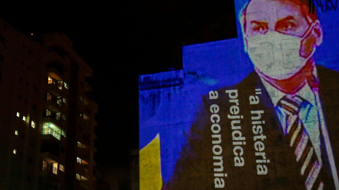 "An image of Brazil's President Jair Bolsonaro and the phrase ""Hysteria Damages the Economy"" is projected as a protest against his handling of the coronavirus COVID-19 outbreak, in São Paulo, Brazil, March 21, 2020."