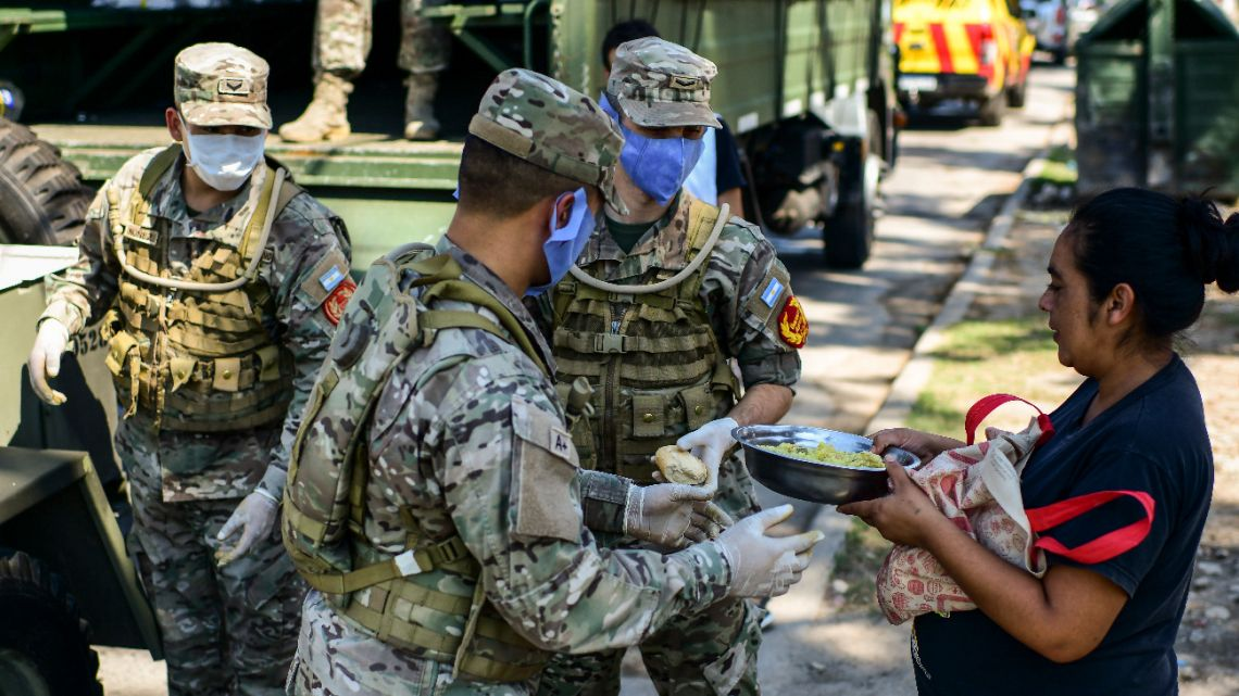 Soldiers give out food to people in a deprived neighbourhood of the municipality of Quilmes, on the outskirts of Buenos Aires, on March 24, 2020, amid the novel coronavirus, COVID-19, pandemic.