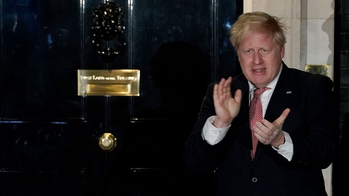 A handout picture released by the UK government on March 26, 2020, shows Britain's Prime Minister Boris Johnson applauding on the step of 10 Downing Street in appreciation of the National Health Service (NHS).