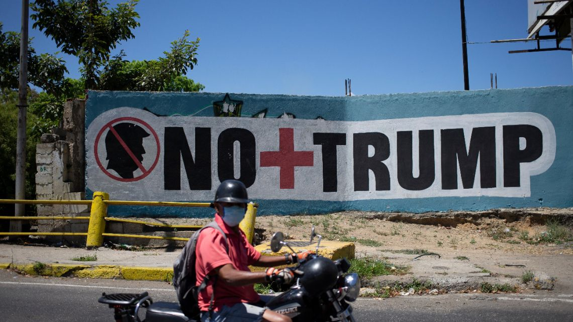 "A man wearing a face mask as a precaution amid the spread of the new coronavirus passes a mural that in Spanish reads "" No more Trump"" in Caracas, Venezuela, Friday, March 27, 2020."