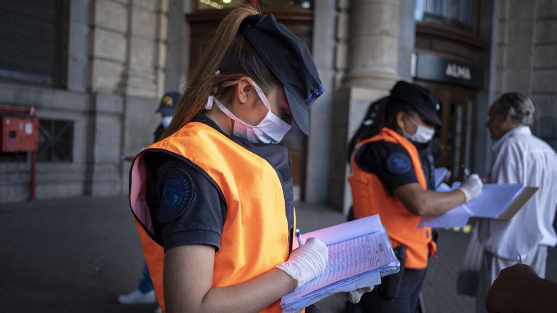 A police officer checks papers at Retiro station.